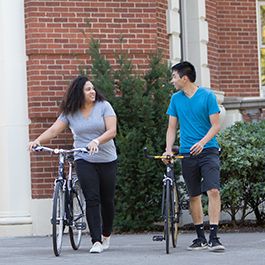Two summer session students walk their bikes next to each other and talk.