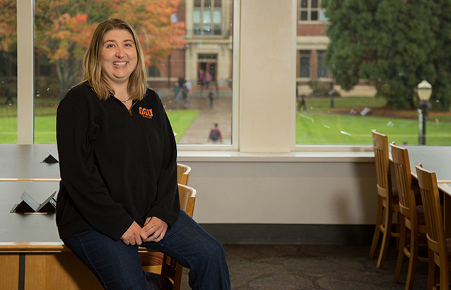 Theresa Harper sits on the corner of a table in the Oregon State University Valley Library. She wears a black long-sleeved shirt with a small OSU logo.