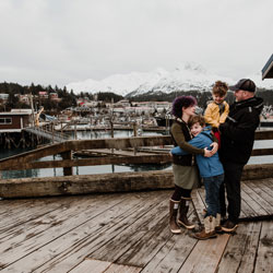 Tommy Sheridan and his family stand on a dock in front of a snowy mountain and a town in the distance. From his home in Alaska, Tommy earned a Fisheries Management Graduate Certificate in 2012 and a Professional Science Master's in Fisheries and Wildlife Administration in 2017.