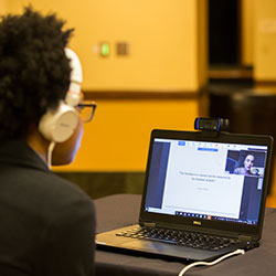 A person with curly hair and white headphones looks attentively at a laptop screen where Ecampus anthropology student Victoria Keenan presents her research remotely from the UK at the Celebrating Undergraduate Excellence event.