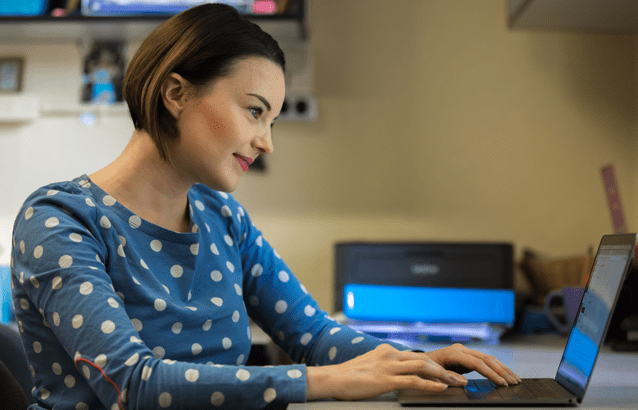A side profile of Oregon State Ecampus student Victoria Keenan. She sits at a desk with her hands placed on the keyboard of a small, black laptop. She wears a blue shirt with white dots and smiles slightly.