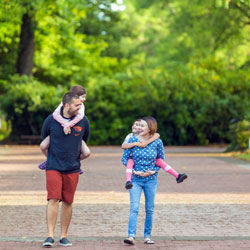 Victoria and her family walk on the Oregon State University Corvallis campus. Victoria and her husband each carry one of their two children on their back as they face one another smiling.