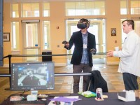 Warren Blyth helps an Ecampus instructor use a virtual reality headset and controls in an educational setting.