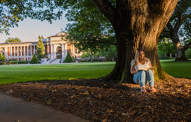 Lucas' winning photo shows a college-age woman (his girlfriend) sitting against a large tree with the Memorial Union in the background. She has a book open atop her knees.