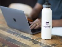Student working on a laptop while seated at a table, with an Oregon State Ecampus water bottle in the foreground