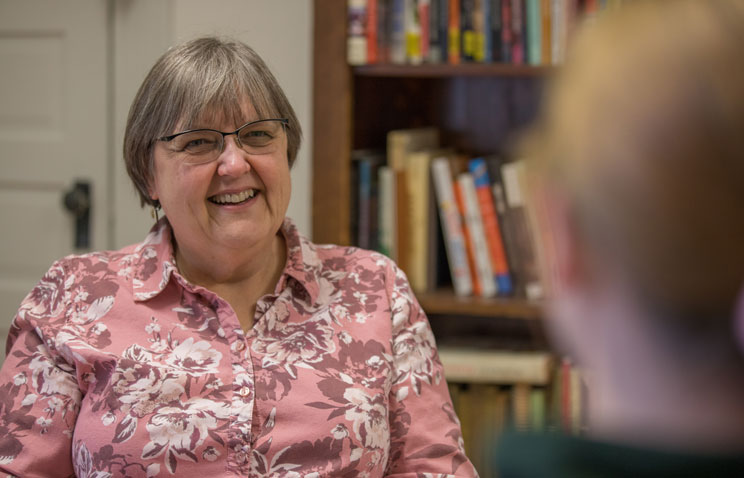 Brenda Kellar, Ecampus anthropology advisor, sits in front of a bookshelf smiling at a person sitting across from her.