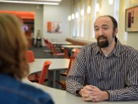 Speech communication professor Colin Hesse wears a brown button-up shirt with white horizontal stripes and his hands are folded on a curved white table in front of him. He is speaking to a person across the table whose head and shoulders are visible from behind. The person has shoulder length reddish-brown hair with light green roots and they wear a dark blue denim jacket. In the background, there is a room with more white tables and red rolling chairs.
