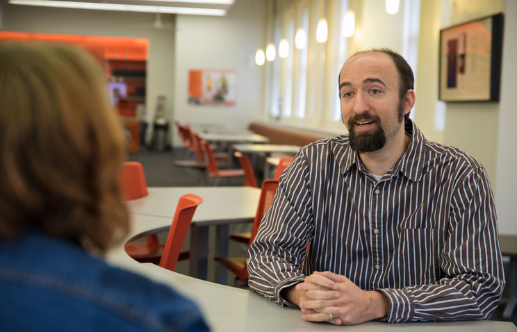 Speech communication professor Colin Hesse speaks with a student sitting across from him at a table in the College of Liberal Arts building.