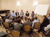 A group of seventeen post-baccalaureate computer science students are seated in a loose circle, discussing benefits, questions and concerns regarding the online program with faculty members at the Computer Science Career Showcase.