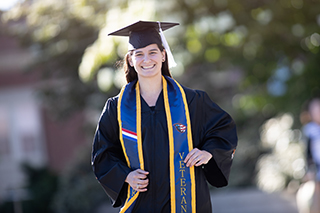 Hope Nelson, Oregon State University Ecampus German graduate, standing in her graduation cap and gown.