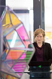 Ecampus engineering management student Ingrid Scheel stands on a balcony with a glass barrier. She is partially covered by a multi-colored glass sculpture that has a metal frame.