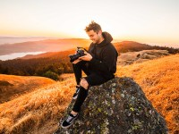 Photographer Jake Chamseddine sits on a rock atop a hill, holding a camera. Jake is a graduate of Oregon State University's digital communication arts bachelor's degree program.