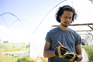 Joshua Chan Burgos writes on a notepad at OSU's Oak Creek Center for Urban Horticulture.