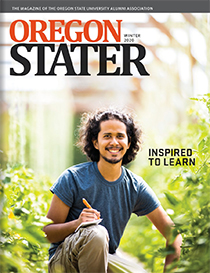 Joshua Chan Burgos kneels in a greenhouse, with pencil and pad in hand, on the cover of the Oregon Stater alumni magazine.