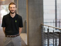 Justin Wolford, an instructor in the Oregon State Ecampus post-baccalaureate computer science program online, stands on an indoor balcony wearing a black polo shirt.