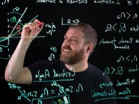 Oregon State physics instructor K.C. Walsh writes on a lightboard.