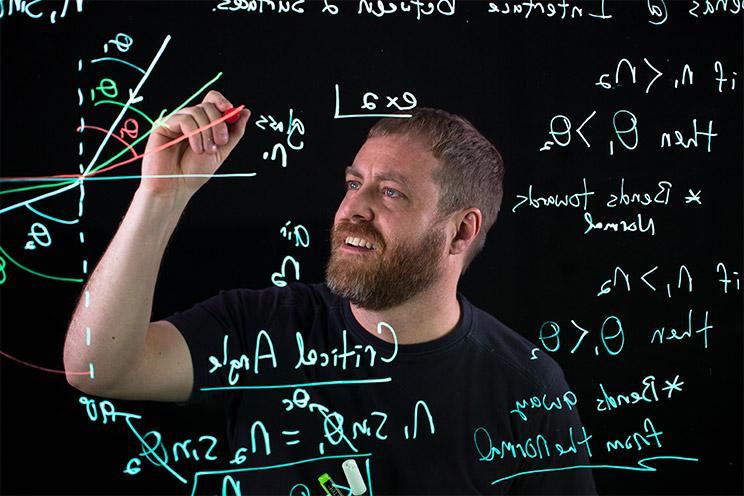 Oregon State physics instructor K.C. Walsh writes on a lightboard.