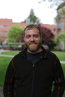 Oregon State University physics instructor K.C. Walsh wears a black zip-up coat and smiles as he stands on the Oregon State Corvallis campus with a lawn and brick buildings behind him.