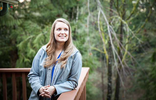 Ecampus student Michelle Cramer leans against a wooden deck with a forested area in the background.