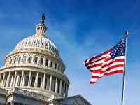 Photo of the U.S. Capitol Building, with the American flag waving in the foreground. Oregon State online political science