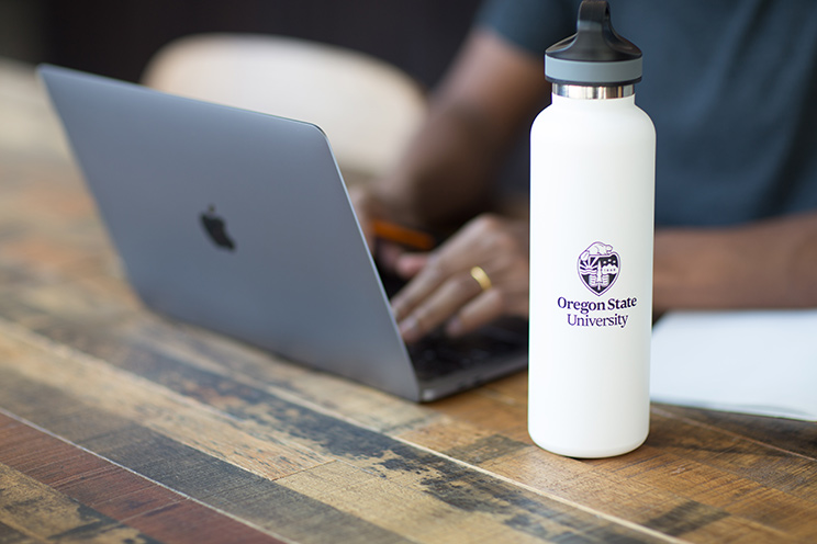 A person sitting at a table and typing on a laptop, with an Oregon State University water bottle in the foreground. K-12 remote instruction resources