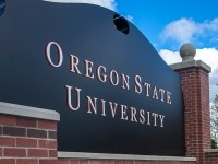 A black sign in gold lettering that reads that Oregon State University, which serves Native and Indigenous students through online education and support