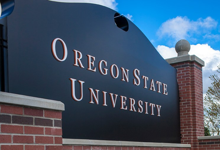 A black sign in gold lettering that reads that Oregon State University, which serves tribal communities through online education and support