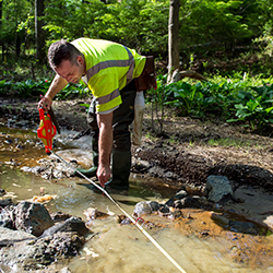 Orman wears a neon green work vest and leans over a shallow stream with a measurement tool.