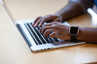 A person's hands are seen typing on a laptop computer