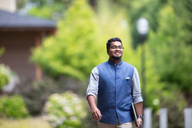 Oregon State Ecampus graduate Patric Papabathini walks forward with a smile on his face and a laptop carried under his left arm. He is wearing a half-sleeve, light blue button-up shirt under a dark blue Nehru collar vest with a handkerchief in the breast pocket.