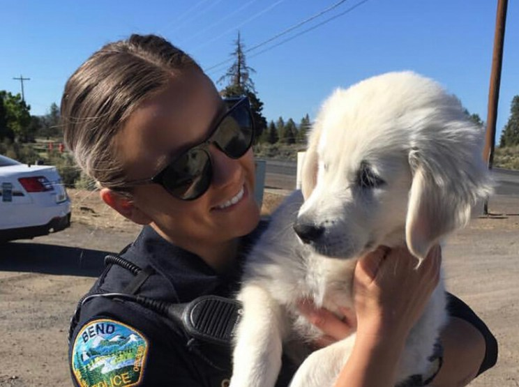 Oregon State University Ecampus graduate Caitlin Brooks, then a police officer in central Oregon, holds a white dog. She studied business administration online.