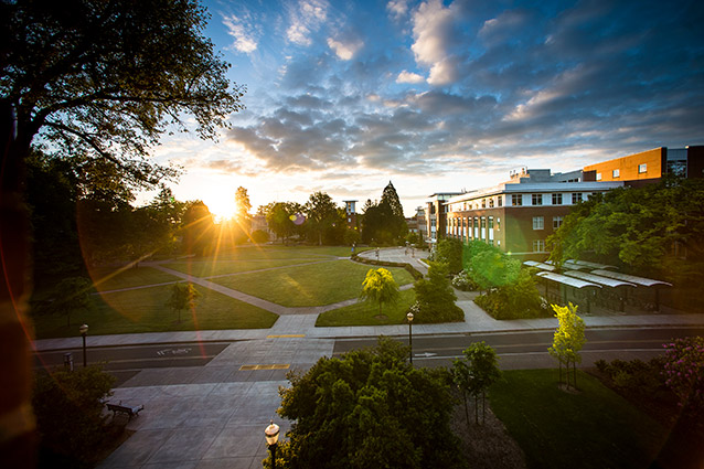 The Valley Library quad at Oregon State University is photographed from a high vantage point. There are clouds in the sky and the sun is shining brightly through trees at the edge of the quad.