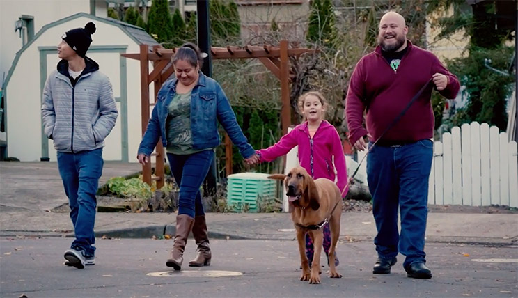 Todd Van Hess, Oregon State Ecampus business administration graduate, walks down the street with his family and dog.