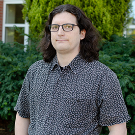 Photo of Zach Welhouse, the online learning librarian for OSU Libraries, standing outside the Valley Library.