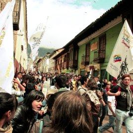 Manifestantes pacíficos escapan gas lacrimógeno lanzado por la policía en la Plaza de Bolívar.