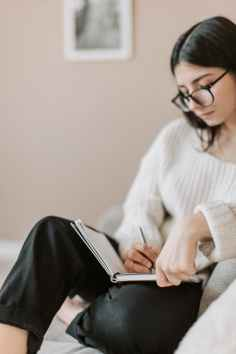 Image displays woman sitting on a couch writing in a notebook or journal. Let's imagine she is working on interview prep for her next job.