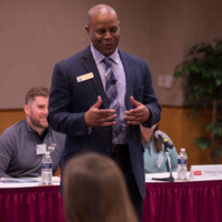 Image of Dr Calvin Williams speaking at a conference animatedly and happily. Image is here to shine focus on the author of Professional Networking.