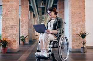 This young woman sitting on wheelchair while using laptop is preparing for employment in the business sector.