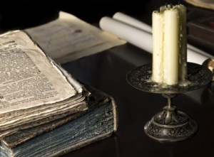 Detail of a medieval study showing antique documents and candle