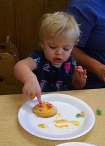a child enjoying the texture of food with her fingers