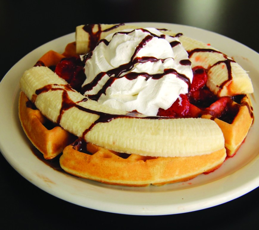A waffle topped with a split banana, red strawberries, whipped cream and a drizzle of chocolate sauce