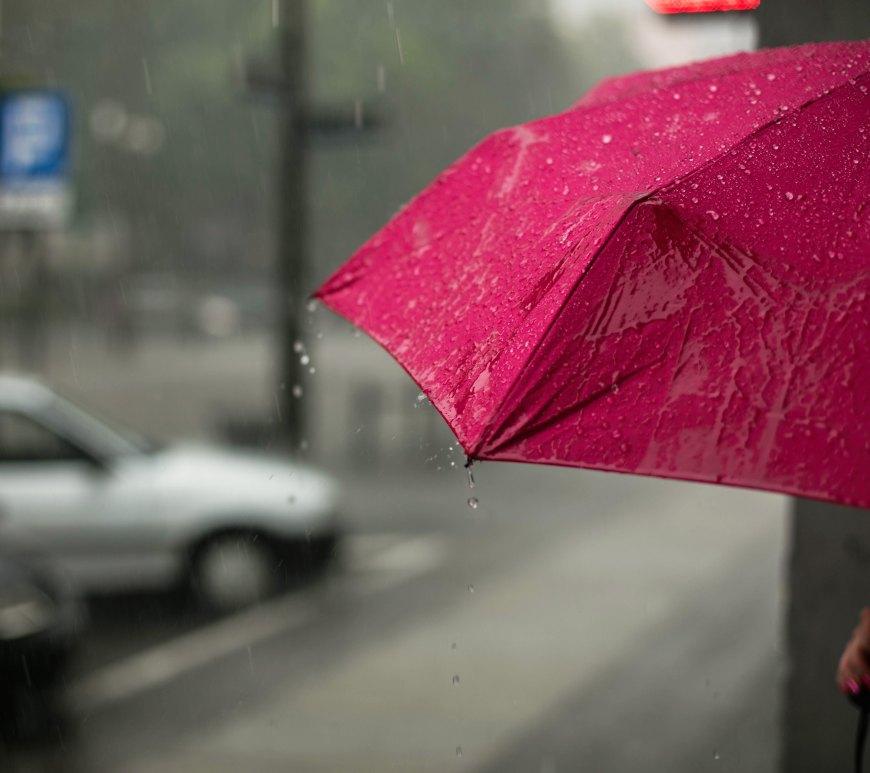 red umbrella under heavy rain