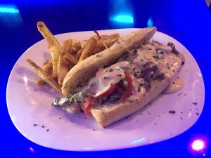 Philly Cheese steak on plate with seasoned fries