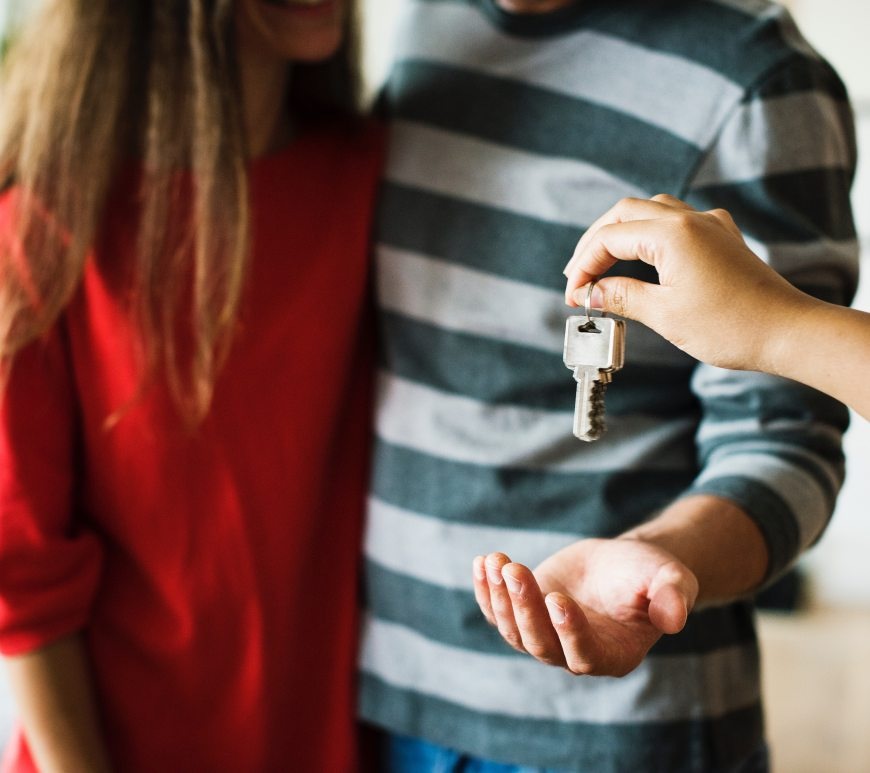 Happy couple being handed keys to new home, homebuyers