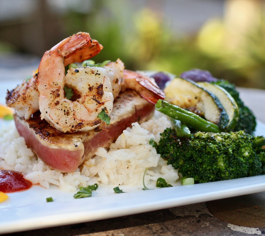 grilled shrimp and seared tuna steak atop bed of rice with vegetables