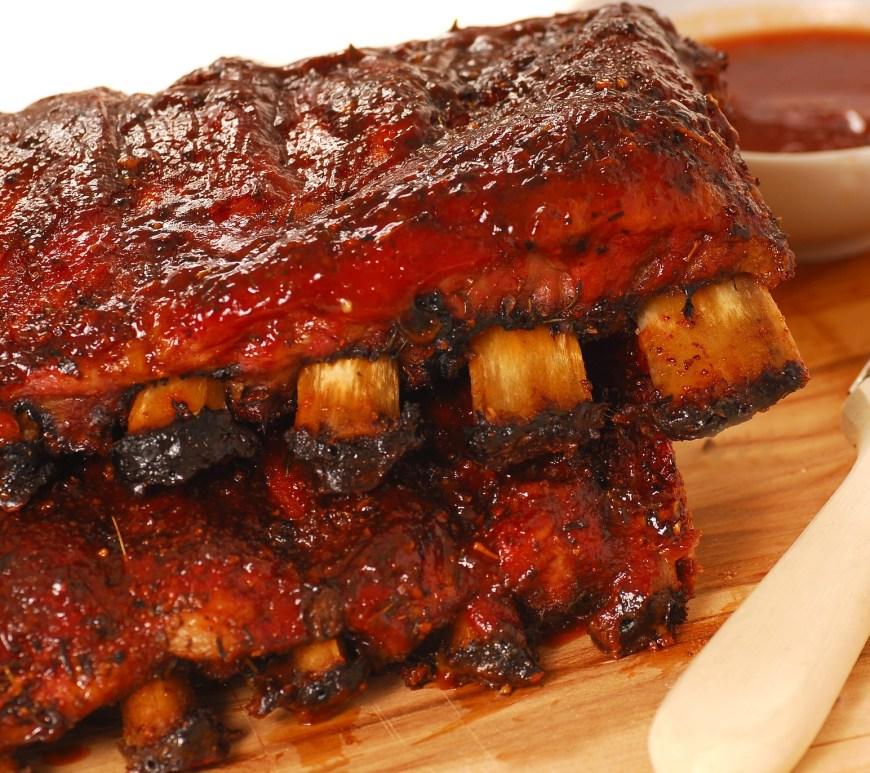 ribs on the bone on wooden cutting board