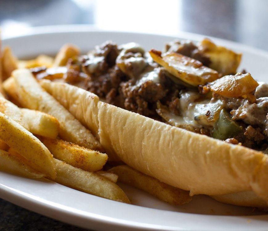 Philly cheesesteak and fries on white plate