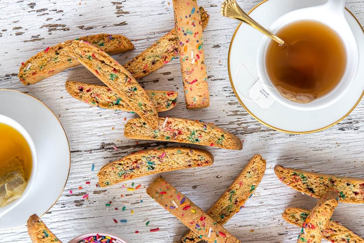 rainbow biscotti with cups of tea on wood table