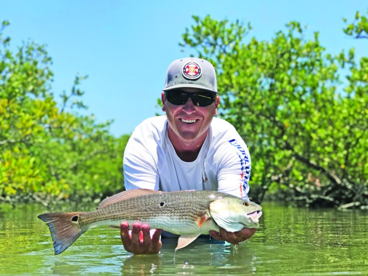 Tyler Chestney fishing in backwater creek holding large fish