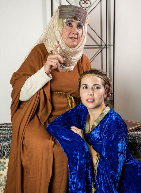older woman and younger woman look off camera in medieval dress